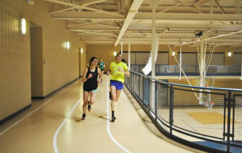 The women's track and field team trains Jan. 16 in the Wellness Center, running laps around the track above the gym.