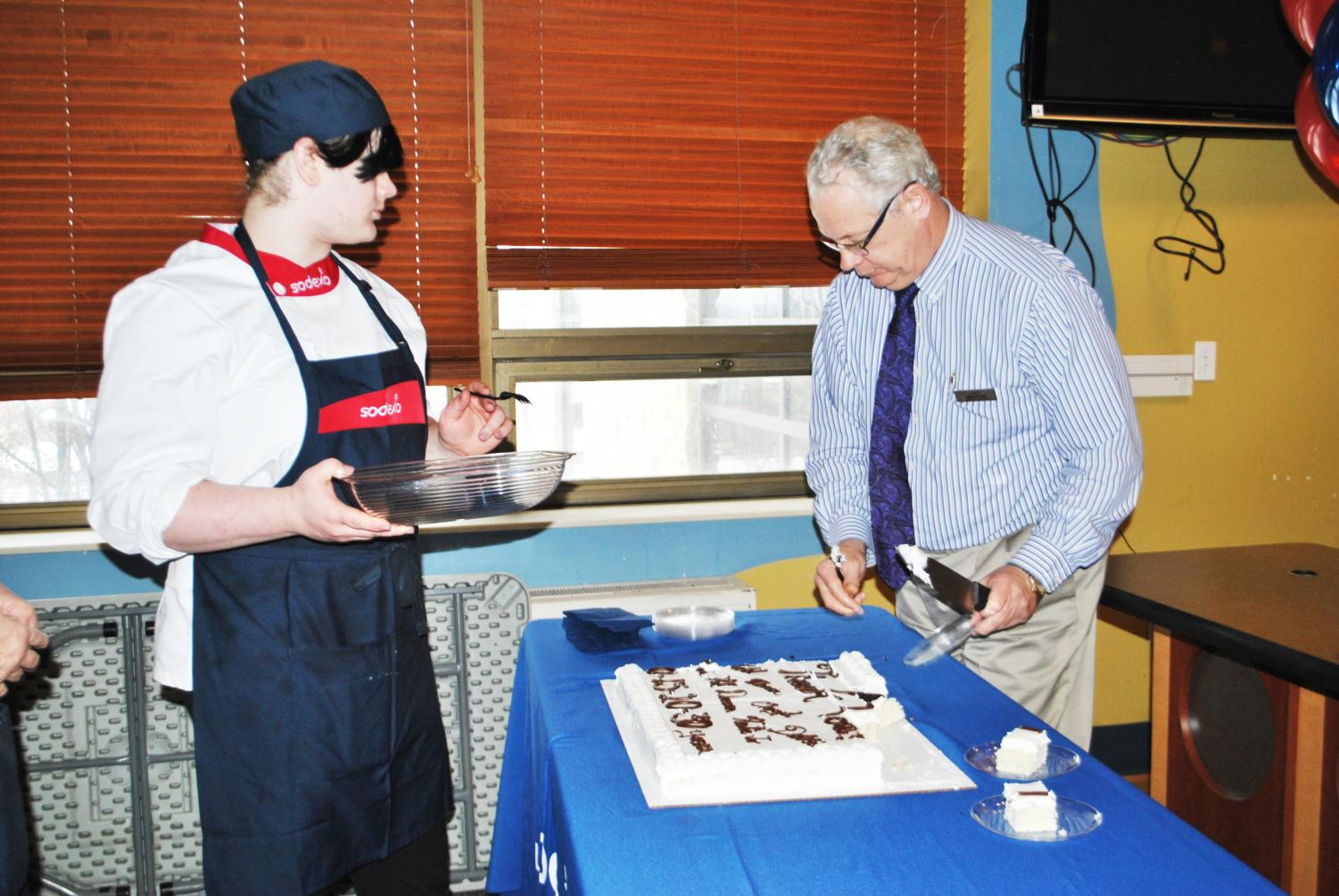Sodexo General Manager Jim Butler (right) cuts a cake for a Sodexo staff celebration Feb. 11 in the Mt. Cat Club while Sodexo employee Solaris Deffenbaugh (left) waits for a piece.