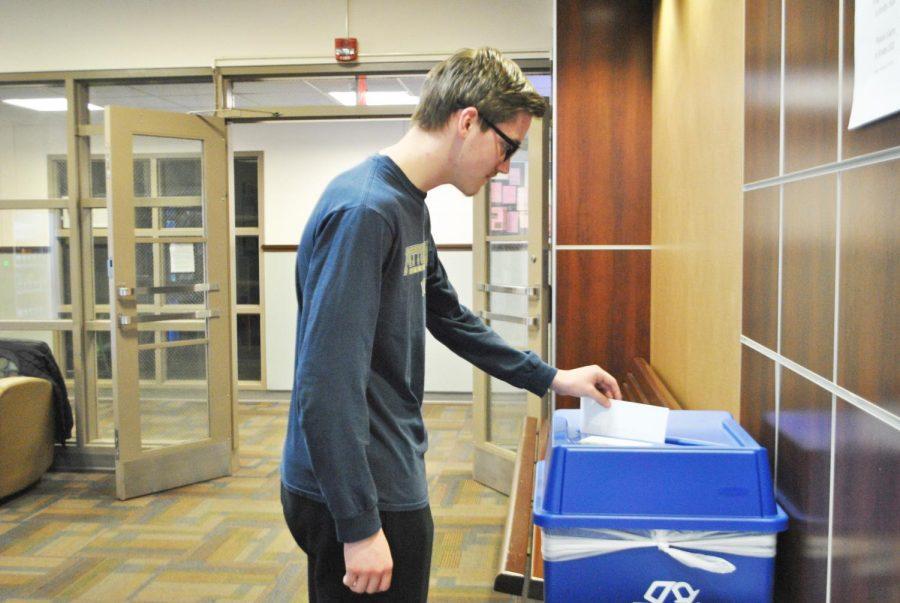 Freshman Adam Bambino uses a recycling bin Friday in Krebs Hall.