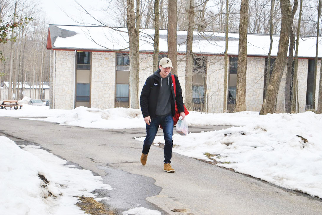 Senior John Knox walks past freshman dorms Feb. 22 on his way to Willow Hall.  Weather conditions are getting better after several people reported falling on icy sidewalks last week.
