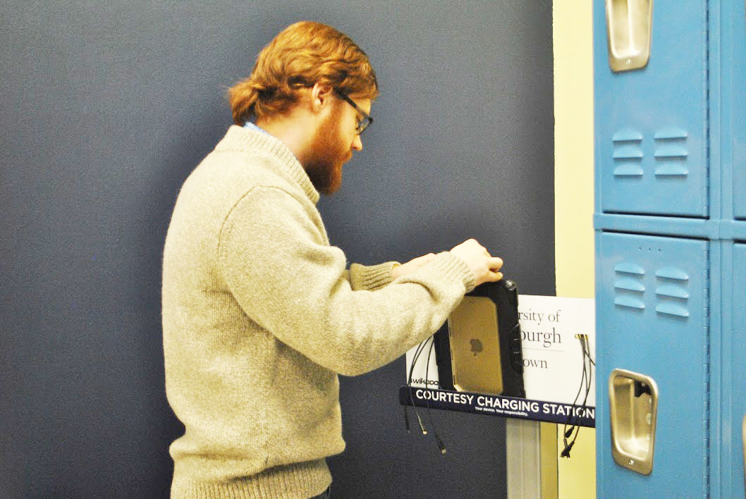 Senior Patrick Stahl charges his iPad at the charging station in the commuter lounge in the Student Union Feb. 1.  An additional charging station is to be added to the Tuck Shop seating area in the Student Union this week.
