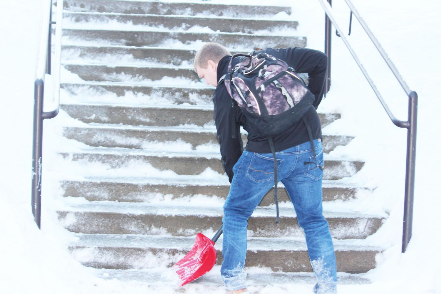 Junior Ryan Stewart shovels snow on Living/Learning Center stairs Feb. 1 with a shovel he purchased from Walmart.
