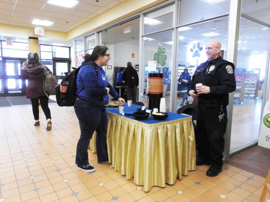 Junior Abby Gontis (left) talked with police officer Glenn Berkey (right) and had a cookie and a cup of coffee Feb. 27. outside the Tuck Shop.