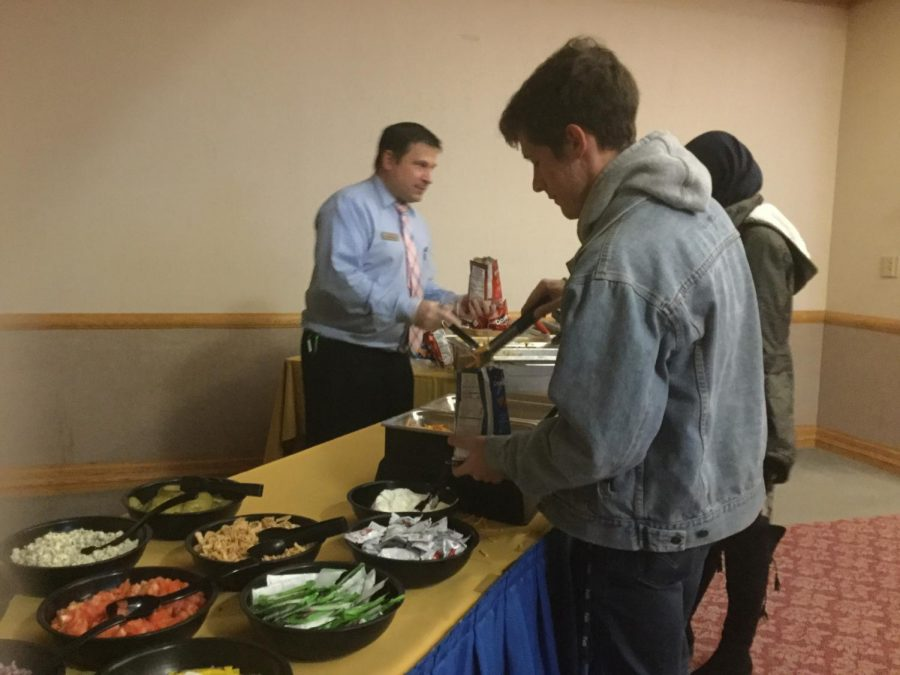 Sophomore Devin Seiger makes a Walking Taco served by Sodexo Catering Manager Derek Krajc at the Pitt Day of Giving party Thursday.