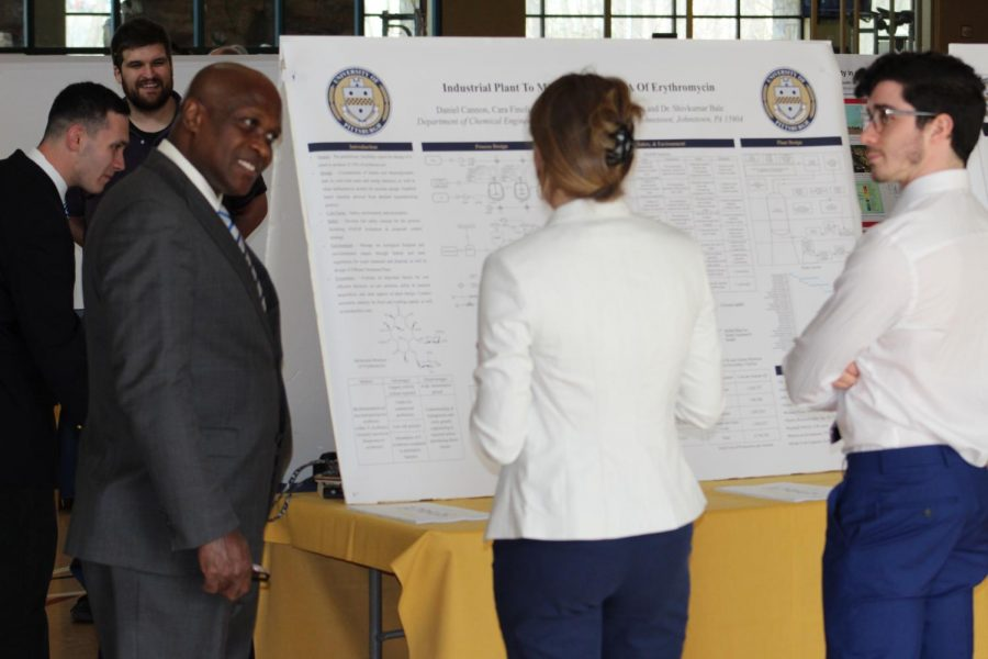 Pitt-Johnstown President Jem Spectar (left) views student research April 10 in the Wellness Center.