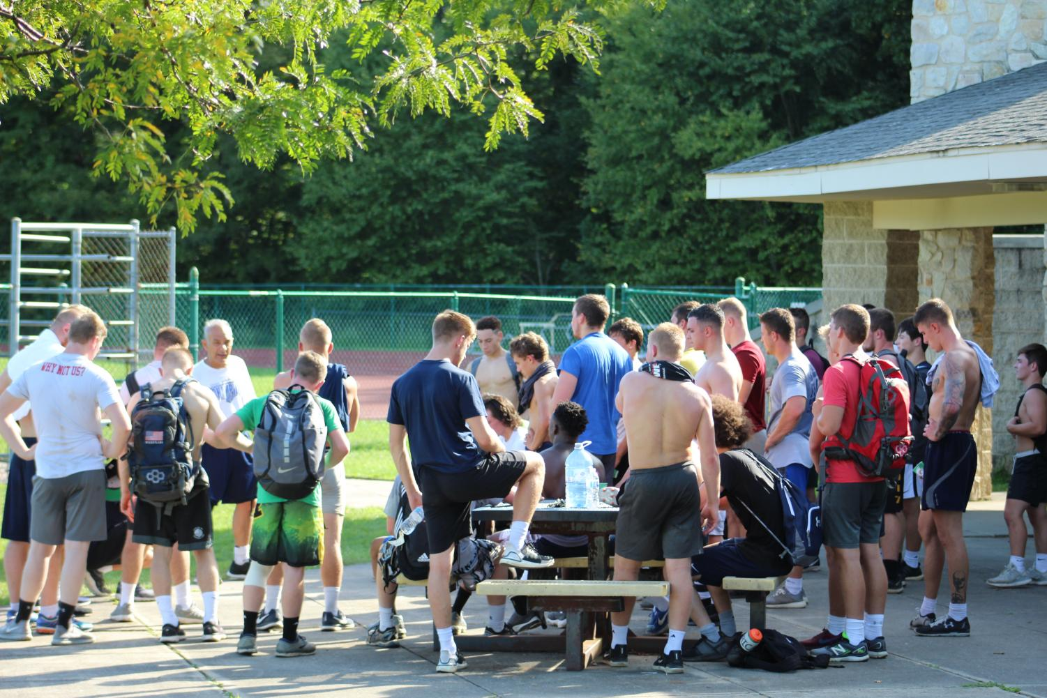 Pitt-Johnstown's head wrestling coach Pat Pecora (fifth from left) holds a team meeting after preseason training concluded adjacent to the Pitt-Johnstown outdoor track Sept. 3.