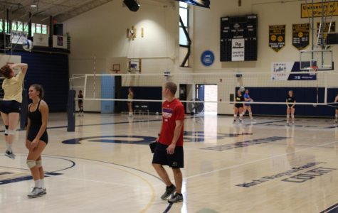 Head Volleyball coach Justin Haupt (middle) oversees practice of the Pitt-Johnstown volleyball team for the coming tournament Sept. 12 at the Sports Center.