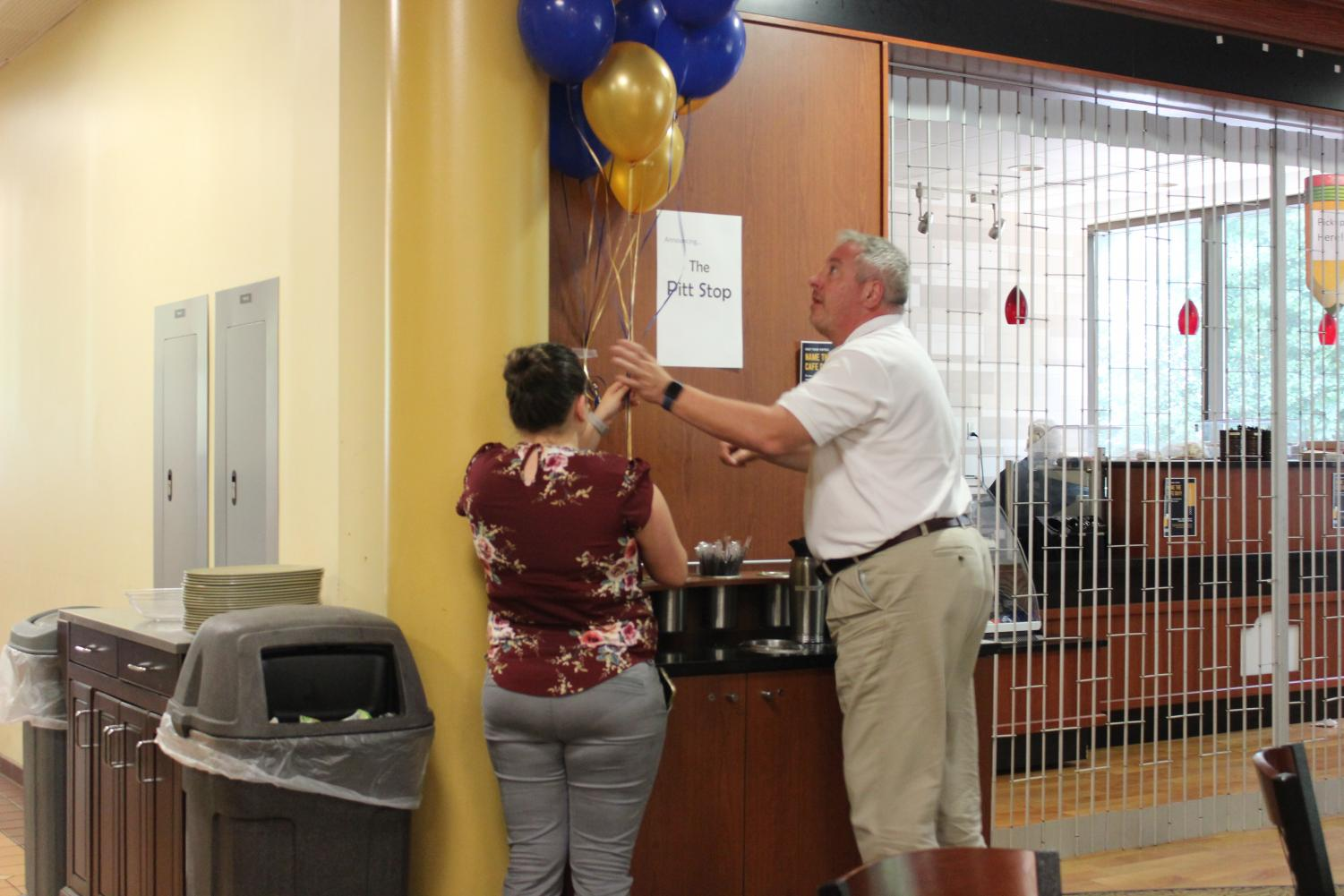 Sodexo Unit Marketing Coordinator Emily Cairns (left) and Dining Services Director Bob Knipple (right) arrange balloons next to a sign announcing the new café's name, the Pitt Stop.