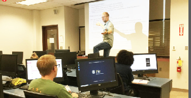 Writing Professor Eric Schwerer teaches his Intro to Professional Writing class Oct. 3. He said encourages students who are struggling academically.