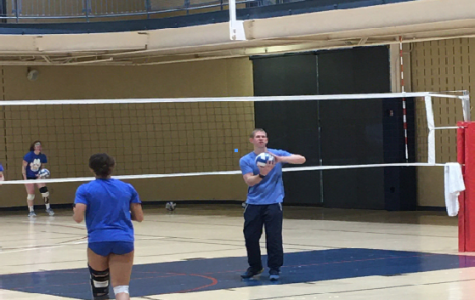 Justin Haupt (right), coaches the women's volleyball team in the Wellness Center.