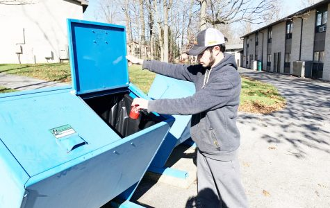 Junior Brennan Brokaw recycles in the pale blue bins near the Summit townhouse Sunday. Brokaw said that this was his first time using the bins, because he thought that the bins were mailing bins as opposed to recycling bins.