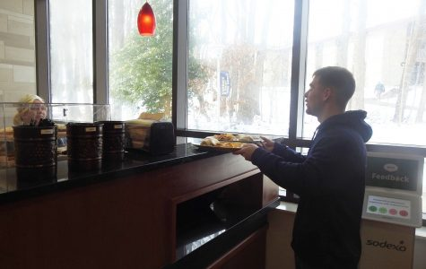 Senior Joe Romano picks up his food Jan. 9 at the Pitt Stop café where students can exchange one meal swipe per meal period for a combination of food options.