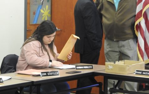 Freshman Hannah Ribblett prepares for a Jan. 9 Conemaugh Valley School Board meeting as Superintendent Shane Hazenstab (left) and board President Todd Roberts (right) have a conversation in the background.